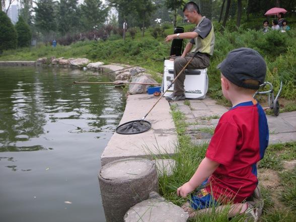 Junior titter på noen som fisker i Lido Side Park