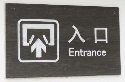 Et kinesisk skilt som viser hvor inngangen er.